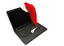 Christmas laptop. Christmas notebook with red hat. Isolated on white background Stock Photography