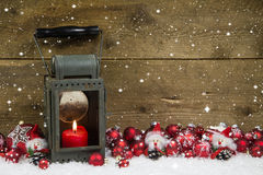 Christmas latern with red candle and balls on wooden background. Stock Image