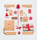 Christmas layout with craft paper wrapping gift boxes, tags, cookies, red holiday decoration, present, spices, Santa hat Royalty Free Stock Image