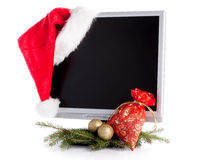 Christmas LCD monitor. Modern flat screen LCD monitor in Christmas red hat with branch of fir-tree on a white background Stock Image
