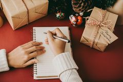 Christmas letter. Close-up image of woman writing Christmas letter in notepad Royalty Free Stock Images