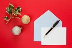 Christmas letter over a red background. Christmas letter and pen over a red background with decorations Royalty Free Stock Photo