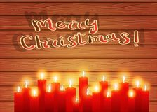 Christmas night. Burning candles on a wooden background. Celebra. Christmas letter. Red burning candles on a wooden background. Christmas background. A postcard Stock Photo