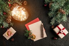 Christmas letter for Santa on dark background with gifts, fir branches, pine cones, glowing ball. Xmas and Happy New Year theme. Flat lay, top view royalty free stock image