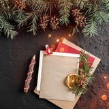 Christmas letter for Santa on dark background with pencil, fir branches, pine cones. Xmas and Happy New Year theme, bokeh, sparkin. G, glowing. Flat lay, top stock photo