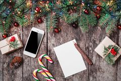 Christmas letter on wooden background with mobile phone, gifts, candy, Fir branches, red decorations. stock images