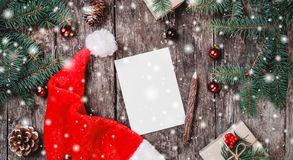 Christmas letter on wooden background with red Santa hat, Fir branches, pine cones, red decorations royalty free stock image