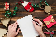 Christmas letter writing. On white paper on wooden background with decorations Royalty Free Stock Photos