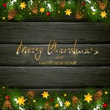 Christmas lettering on black wooden background with fir tree bra Stock Photography
