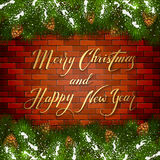 Christmas lettering on brick wall background with fir tree branch. Holiday lettering Merry Christmas and Happy New Year on a brick wall background with winter Stock Photography