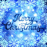 Christmas lettering inscription on blue background. Christmas lettering inscription on abstract glowing background with glittering confetti elements and Royalty Free Stock Image