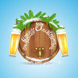 Christmas lettering on wood barrel with snowy fir tree branch and beer of glass. On blue background Stock Photography