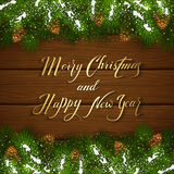 Christmas lettering on wooden background with fir tree branches. Holiday lettering Merry Christmas and Happy New Year on brown wooden background with winter Royalty Free Stock Images