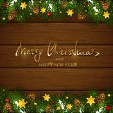 Christmas lettering on wooden background with fir tree branches. Text Merry Christmas and Happy New Year on brown wooden background with holiday decorations Stock Photos