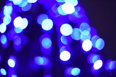 Christmas light background. Decorated trees. Holiday glowing backdrop on the dark blue night sky. Defocused background. blurred stock photography