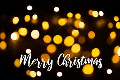 Christmas light background. Holiday Glowing Background. Defocused background with blinking stars. Blurred bokeh. With the. Inscription Happy Christmas stock image