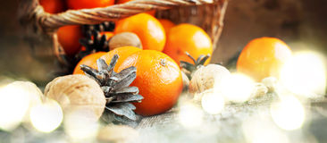 Christmas Light with Basket of Festive Food on wooden background. Christmas Light with Basket of Festive Food, Fruits and Nuts. Tangerines, Pine cones, Walnuts royalty free stock image