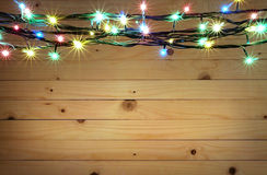 Christmas light boarder on wooden background. Royalty Free Stock Photo