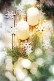Christmas Light with Bokeh and White Burning Candles on Wooden Background Stock Images