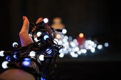 Christmas light bulbs in hands Stock Photo
