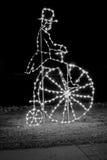 Christmas Light Display B&W. Black & White Christmas lighting shaped like an old fashion man & large wheel bike, in local park Royalty Free Stock Photography