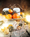 Christmas Light on Festive Table with Tangerines, Pine cones, Walnuts, Candles. Holiday decorations Royalty Free Stock Photo