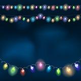 Christmas light garland on the night sky. Stock Photos
