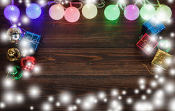 Christmas light and gift ornaments on old wood background. Stock Images