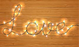 Christmas light on love sign with wooden background Stock Image