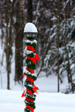 Christmas Light Pole. Outside light pole decorated for Christmas with red ribbon and green garland in the snow Stock Images