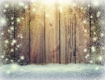 Glow of festive lights and a wooden background in the snow. Chr Stock Images