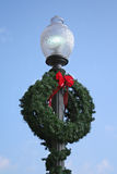 Christmas Light Wreath. Old city street lamp decorated with a holiday wreath, against blue sky. Vertical format Royalty Free Stock Photos