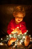 Christmas Lights. Child playing with Christmas lights Royalty Free Stock Photography