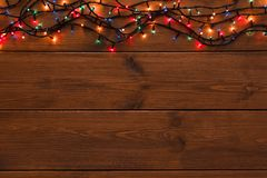 Christmas lights border on wood background. Christmas lights background, copy space. Holiday shiny colorful garland border top view on brown wooden planks royalty free stock photography