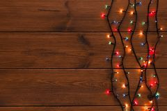 Christmas lights border on wood background. Christmas lights background, copy space. Holiday shiny colorful garland border top view on brown wooden planks Stock Images