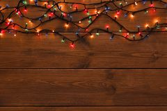Christmas lights border on wood background. Christmas lights background, copy space. Holiday shiny colorful garland border top view on brown wooden planks Stock Photos