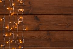 Christmas lights border on wood background. Christmas lights background, copy space. Holiday shiny garland border top view on brown wooden planks surface. Xmas Royalty Free Stock Image