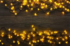 Christmas lights border on grey wooden background. Christmas lights background, copy space. Holiday shiny garland border top view on dark grey wooden planks Royalty Free Stock Image