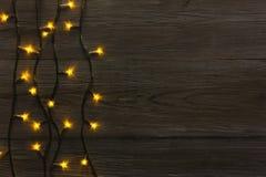 Christmas lights border on grey wooden background. Christmas lights background, copy space. Holiday shiny garland border top view on dark grey wooden planks Royalty Free Stock Photos
