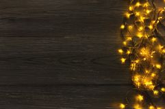 Christmas lights border on grey wooden background. Christmas lights background, copy space. Holiday shiny garland border top view on dark grey wooden planks Royalty Free Stock Images