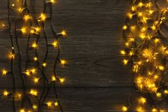 Christmas lights border on grey wooden background. Christmas lights background, copy space. Holiday shiny garland border top view on dark grey wooden planks Stock Images