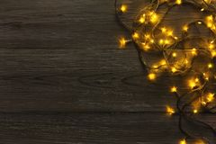 Christmas lights border on grey wooden background. Christmas lights background, copy space. Holiday shiny garland border top view on dark grey wooden planks Royalty Free Stock Photo