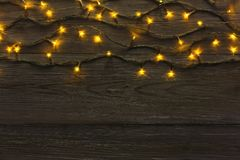 Christmas lights border on grey wooden background. Christmas lights background, copy space. Holiday shiny garland border top view on dark grey wooden planks Stock Photography