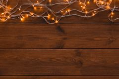 Christmas lights border on wood background. Christmas lights background, copy space. Holiday shiny garland border top view on light brown wooden planks surface Royalty Free Stock Photography