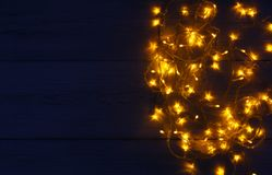 Christmas lights border on wooden background. Christmas lights background, copy space. Holiday shiny garland border top view on wooden planks surface. Xmas tree Stock Photography