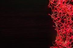 Christmas lights border on dark wooden background. Christmas lights background, copy space. Holiday shiny red garland border top view on dark wooden planks Stock Photos