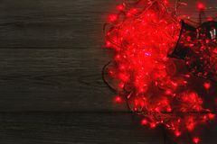 Christmas lights border on wood background. Christmas lights background, copy space. Holiday shiny sparkling red garland border spread from glass jar, top view Royalty Free Stock Images