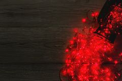 Christmas lights border on wood background. Christmas lights background, copy space. Holiday shiny sparkling red garland border spread from glass jar, top view Royalty Free Stock Image