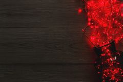 Christmas lights border on wood background. Christmas lights background, copy space. Holiday shiny sparkling red garland border spread from glass jar, top view Royalty Free Stock Photos