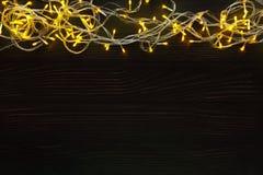 Christmas lights border on dark wooden background. Christmas lights background, copy space. Holiday shiny yellow garland border top view on dark wooden planks Royalty Free Stock Image